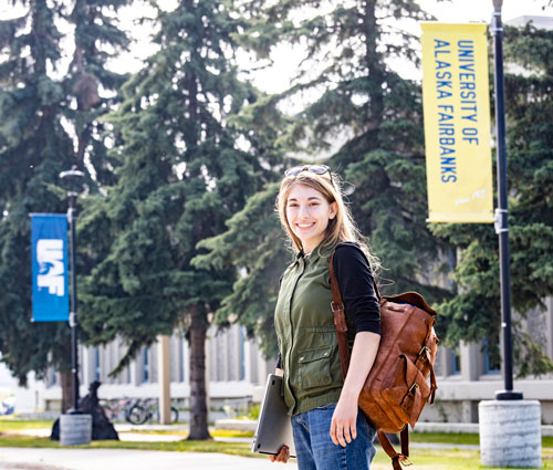 Madeline Burton wearing a backpack and holding a laptop while standing in front of UAF street banner on campus.