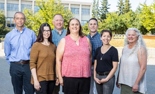 Owen Guthrie, Janene McMahan, Chris Beks, Joanne Healy, Tim Stickel, Kendell Newman Sadiik and Heidi Olson smiling at camera.