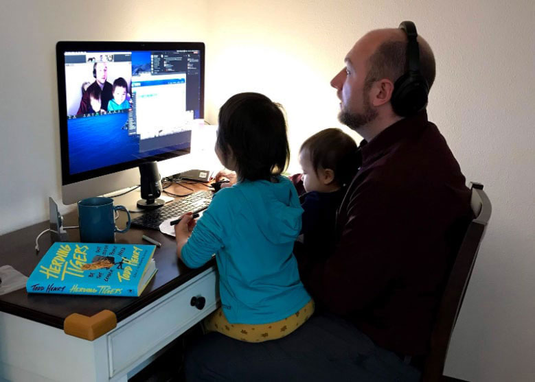 Sean Holland sitting at his home computer with his two daughters on his lap.