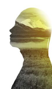 Silhouette of head and shoulders with a calm mountain scene inside.